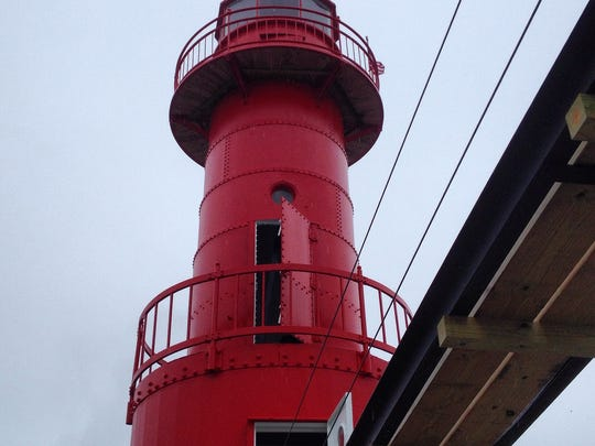 """Red again with its new coat of paint, the former """"Pink Lady"""" rises against the sky."""