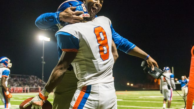 Millville defensive coordinator Lamont Robinson celebrates with Darius Porter (8) during a playoff win in November. On Tuesday,. Robinson was named the head football coach at Washington Township.