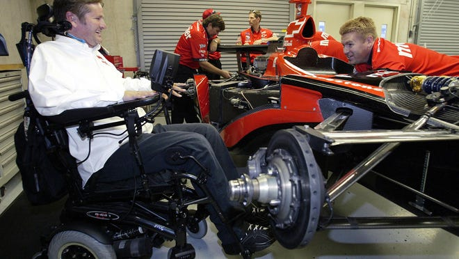 FILE - In this Friday, May 20, 2005 file photo, Indy Racing League car owner Sam Schmidt, left, talks with crew member Mike Sobeleski as he works on the car in the garage area at the Indianapolis Motor Speedway. Sam Schmidt was left quadriplegic from a racing accident and the team he later created has suffered a series of tragedies and setbacks. (AP Photo/Tom Strattman, File)