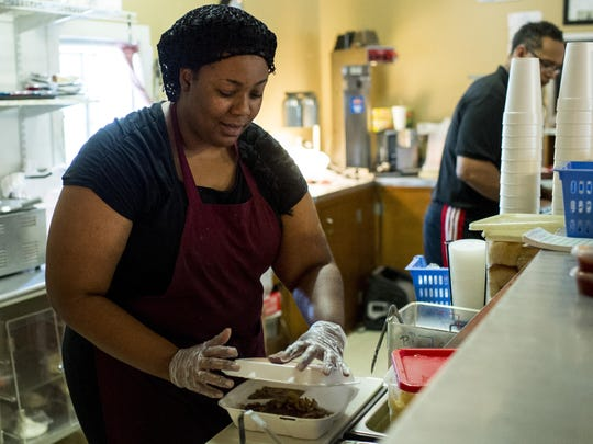 Chyna Washington closes up a plate lunch at Veronica's Cafe in Carencro.