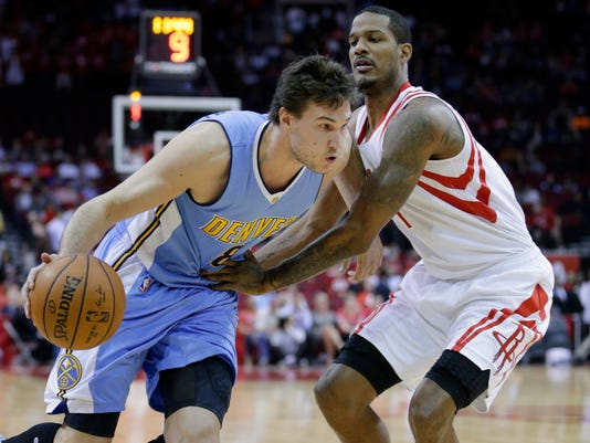Denver Nuggets' Danilo Gallinari (8) drives around Houston Rockets' Trevor Ariza (1) in the first half of an NBA basketball game, Wednesday, April 5, 2017, in Houston. (AP Photo/Michael Wyke)