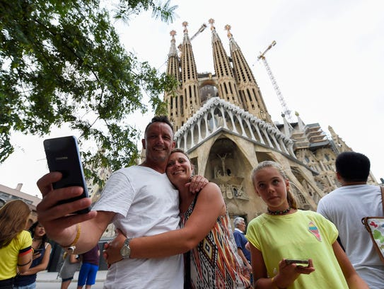 Tourists pose for selfies in front of the Sagrada Familia