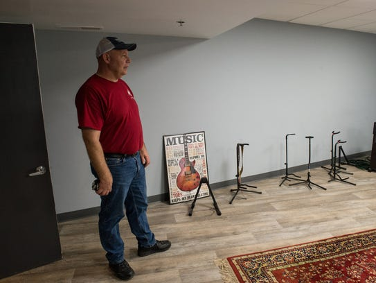 Gino Bailey, owner of AMP Studio, stands in the office