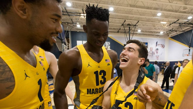 Marquette freshman Ike Eke (center) jokes around with teammates Ed Morrow (left) and Cam Marotta during the the team's media day.