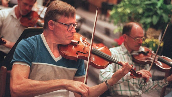 Ralph Hamaker, front, Tom Lange, right, Roger Vogel, left, from the Penfield Symphony Orchestra rehearsal for their first concert of the season at the Browncroft Community Church. 1995 file photo.