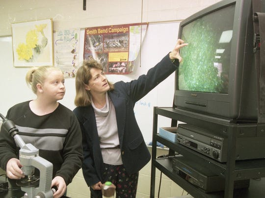 Cassie Plemons, a freshman at Maryville High School, left, looks on as teacher Mary Boldon uses video equipment paid for by the Maryville City Schools Foundation to view the stomata of a fern under a connected microscope in biology class in February 2000.