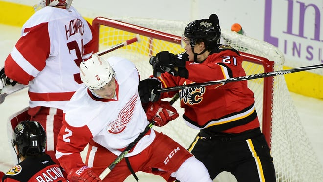 Flames forward Mason Raymond (21) defends against Red Wings defenseman Brendan Smith (2) during the second period of the Wings' overtime loss Friday in Calgary, Alberta.