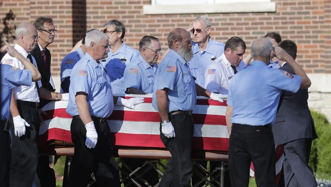 The Town of Oneida Volunteer Fire Department's honor guard escorts the casket of firefighter John Brocker during services Monday in Seymour.