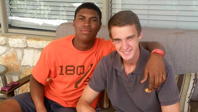 Bakari Henderson (left) sits with his friend Travis Jenkins in this 2016 photo provided by John Gramlich. Henderson was fatally beaten at a bar in Greece on July 7, 2017.
