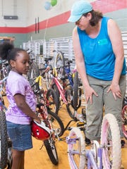 Volunteers help new riders select their bikes at Hands On Nashville's ReCYCLE for Kids giveaway event at Kirkpatrick Community Center. The program, which refurbishes donated bicycles and gives them to local children, has given bikes to more than 700 kids since it began in 2012.