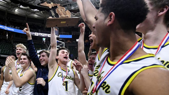 Foster Loyer holds the Class A championship trophy after Clarkston's win over Holland West Ottawa.