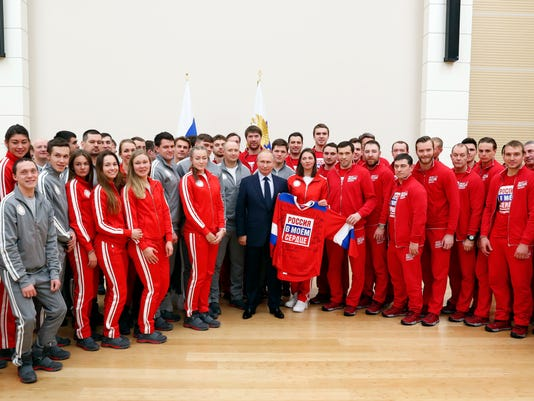 Russian President Vladimir Putin, holds a jersey while posing for a photo the Russian athletes who will take part in the upcoming 2018 Pyeongchang Winter Olympic Games in South Korea, at the Novo-Ogaryovo residence outside in Moscow, Russia, Wednesday, Jan. 31, 2018. (Grigory Dukor/Pool Photo via AP)
