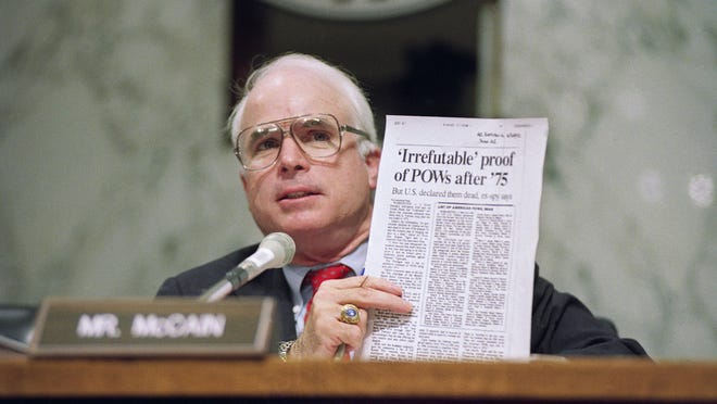 In this June 24, 1992, file photo, Sen. John McCain, R-Ariz., holds up an article from the Washington Times during a hearing of the Senate Select Committee on POW/MIA Affairs on Capitol Hill in Washington.