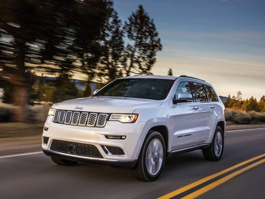 A white Jeep Grand Cherokee, a large crossover SUV, on a country road.