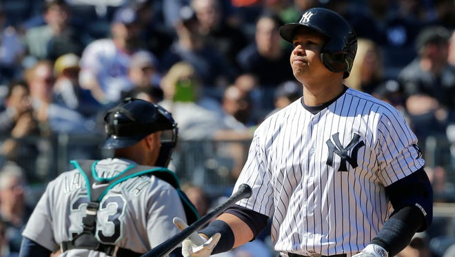 New York Yankees' Alex Rodriguez flips his bat after striking out during the sixth inning of a baseball game as Seattle Mariners catcher Chris Iannetta (33) walks toward the dugout Saturday, April 16, 2016, in New York.