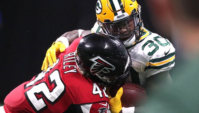 Packers running back Jamaal Williams picks up a first down with Falcons outside linebacker Duke Riley defending.