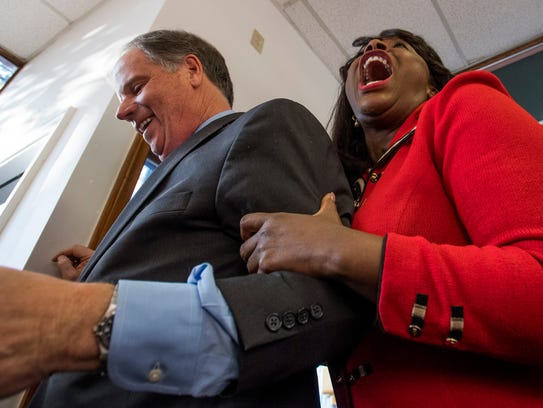 Then-candidate Doug Jones and Rep. Terri Sewell laugh during a rally at his Senate campaign headquarters in Birmingham, Ala., on  Dec. 10, 2017.