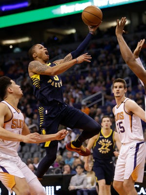 Indiana Pacers guard Joe Young (3) drives against Phoenix Suns guard Devin Booker and Dragan Bender (35) in the first half during an NBA basketball game, Sunday, Jan. 14, 2018, in Phoenix.