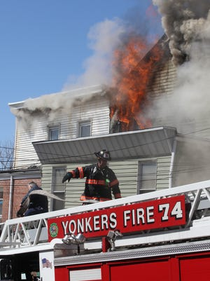 Fire consumes the top floor of 53 Herriot Street as Yonkers firefighters prepare to raise an aerial ladder to battle a four alarm in the city, April 10, 2016.