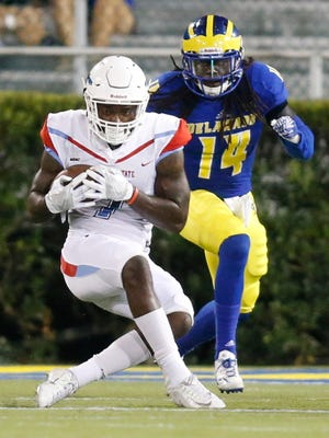Delaware State receiver Aris Scott grabs a pass as Delaware's Simba Gwashavanhu steps up for a tackle in the fourth quarter of Delaware's 56-14 win at Delaware Stadium Thursday.