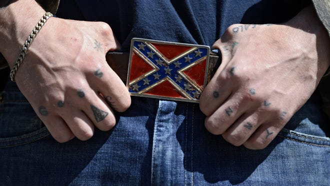A protester holds his Confederate Battle Flag belt buckle while participating in an anti-illegal immigration rally in Atlanta, Georgia in in April 2013.