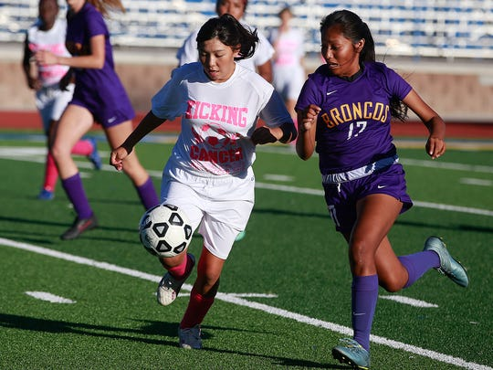 Bloomfield's Telaya Wero, left, and Kirtland Central's Nikki Begay fight for the ball on Tuesday at Bobcat Stadium.