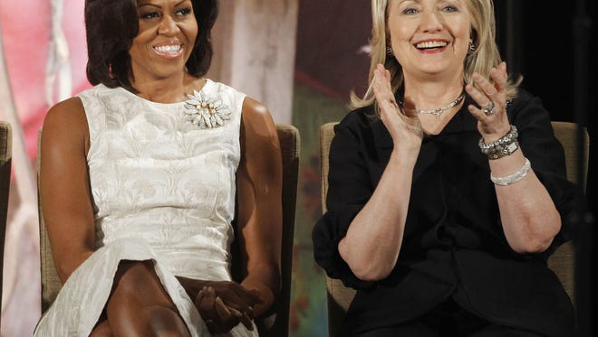 In this March 8, 2012, file photo, then-Secretary of State Hillary Clinton and first lady Michelle Obama attend the 2012 International Women of Courage Awards at the State Department in Washington. Clinton and Obama are slated to campaign together for the first time at a rally in Winston-Salem, North Carolina on Oct. 27, 2016. The event will bring together two women who are a study in contrasts. Clinton is perhaps one of the least traditional first ladies in modern history, while Obama has fully embraced tradition.