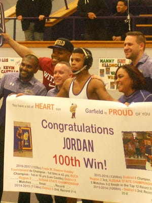 Garfield senior Jordan Robinson celebrating his 100th career victory Jan. 13 with his family and coaching staff.