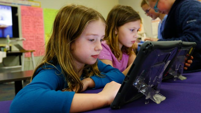 Fourth-graders Emily Weber, 9, left and Gracin Dittmar, 10, work on their iPads on Monday at Odyssey Elementary School in Weston.