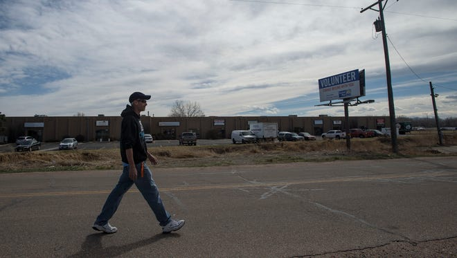 Volunteer at the Fort Collins Cat Rescue, Matt Day, walks down the road during his break on Friday, March 30, 2018, on Frontage Road South, next to East Mulberry Street in Fort Collins, Colo.