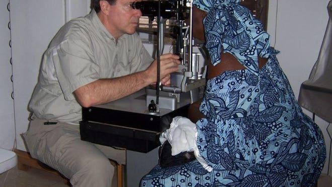 Dr. Karl A. Holzinger examines a patient at the Save the Nation's Sight clinic during a recent trip to Ghana.