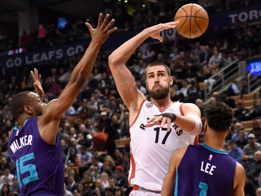 Toronto Raptors' Jonas Valanciunas makes a behind the back pass to teammate DeMar DeRozan, not seen, as Charlotte Hornets' Kemba Walker (15) and Courtney Lee defend during the first half of an NBA basketball game Tuesday, April 5, 2016, in Toronto. (Frank Gunn/The Canadian Press via AP)