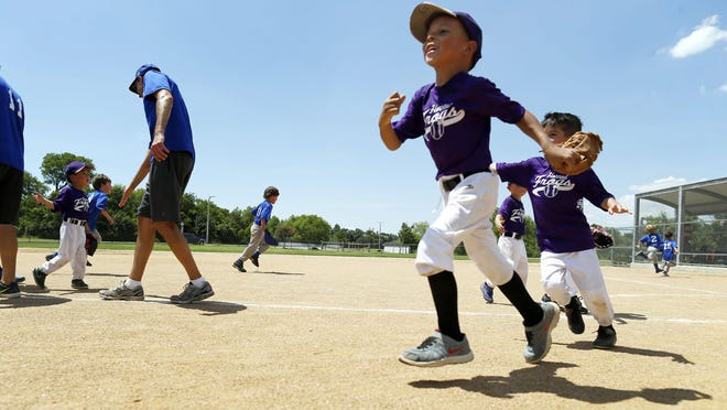 Kingston Robinson runs toward the dugout with his teammates during a tee ball game in Plano, Texas. Kingston is one of more than 115 children in 34 states who became paralyzed last year after developing what seemed like an ordinary cold.