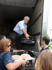 St. Matthew's House CEO Vann Ellison, top, helps unload the refrigerated truck.