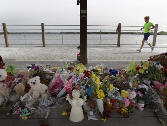 A runner jogs past a memorial on the Fox Cities Trestle