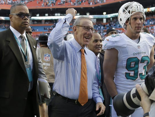 Miami Dolphins owner Stephen Ross, center, walks off
