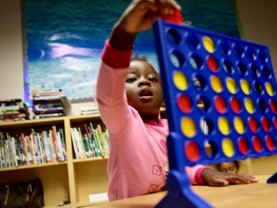 Ivyanna Hall, 2, plays Connect Four with her family