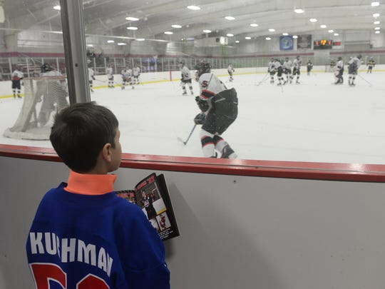 Quinn Kuchman, 8, watches the action as Birmingham United takes on Oxford-Avondale at Birmingham Ice Arena on Jan. 9.