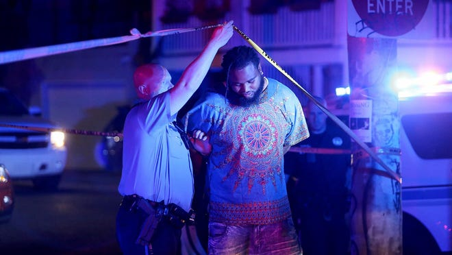 A man is taken into custody early Sunday following a shooting Saturday, April 9, 2016, in New Orleans. Former New Orleans Saints player Will Smith was shot and killed Saturday in what appeared to be a road rage incident that has shocked fans of the much-beloved athlete. Michael DeMocker / The Times-Picayune via AP