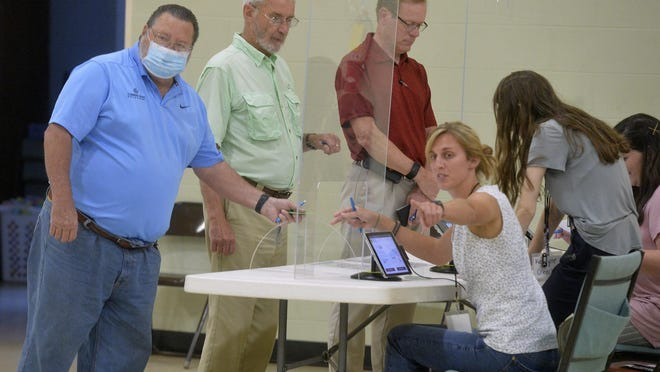 Voters sign in and are directed to the voting machines at Windsor Forest Baptist Church on June 9.