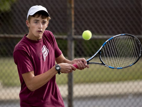 Junior Devon LaHaie returns the ball during tennis