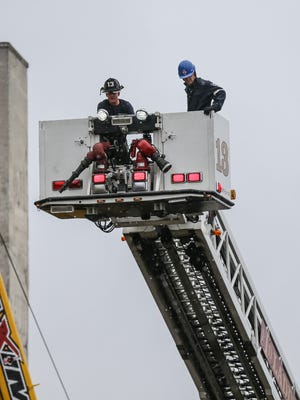 A worker is evacuated after a scissor lift fall at the sight of the former Ford plant on the 1300 block of E. Washington St. in Indianapolis on Monday, April 9, 2018.
