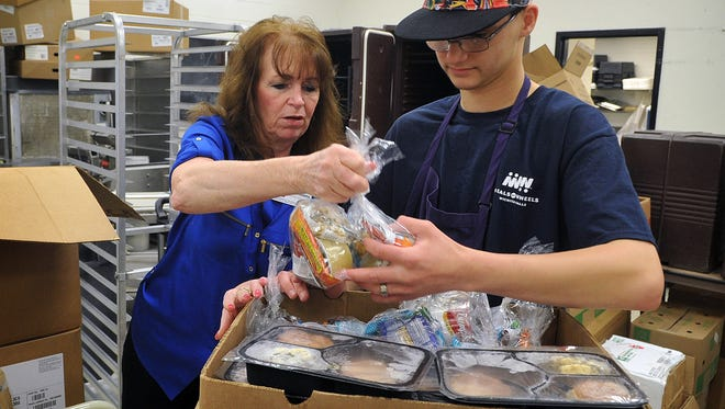 In this file photo, Lisa Williams and Kris Thomas of The Kitchen add frozen meals and non-perishables to cover weekends for Meals On Wheels recipients. The program serves more than 850 clients in Wichita Falls on a daily basis.
