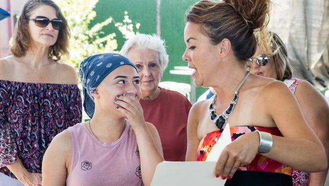 Nevaeh Guzman, diagnosed with alopecia, left, reacts as Marci Dickerson and her nonprofit organization Revolution-120, surprise her with the funds needs for a custom wig on Sunday, July 2, 2018, at The Game II.