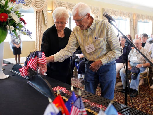 Former prisoner of war Jack Chapman, right, of Santa Fe, N. Mex., with the assistance of Sondra Sortillo, left, places an American flag in rememberance of those who lost their lives both in the war and after returning home during the 39th annual reunion of the Korean War Ex-POW Association held at The Brown Hotel in downtown Louisville. Founded in 1976, this is the final year of the reunion, which honors the veterans and their spouses, surviving widows and family members.  Aug. 2, 2014