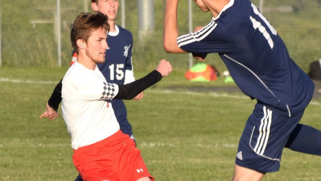 Riverheads' Rinaldo Martina sends the ball to the wing past Page County's Ryan Taylor, center during the first half of their Shenandoah District boys soccer game on Monday, May 8, 2017, at Riverheads High School. The Gladiators won 2-0.