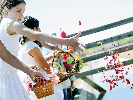 Las Cruces Catholic Schools student McKree Riley tosses flower petals with others at a recent Blessing of the Fields ceremony at New Mexico Farm & Ranch Heritage Museum. Today's ceremony begins at 10 a.m. and is open to all who wish to join the procession.