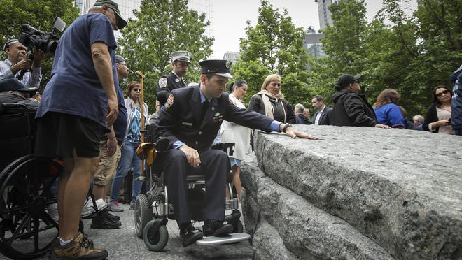 Retired FDNY firefighter and 9/11 first responder Rob Serra touches one of the stone monoliths at the newly dedicated 9/11 Memorial Glade on Thursday in New York.