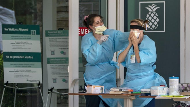 Nurses put on their personal protective equipment Thursday outside the emergency room entrance to Bethesda Hospital West, which is at Boynton Beach Boulevard and U.S. Route 441 west of Boynton Beach.