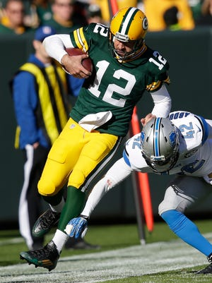 Green Bay Packers quarterback Aaron Rodgers (12) gets bumped out of bounds on a scramble by Detroit Lions strong safety Isa Abdul-Quddus (42) at Lambeau Field November 15, 2015.